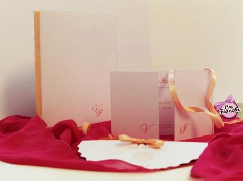 coordinato nozze composto da partecipazione libretto messa e ventaglio in carta con le iniziali degli sposi e nastro di raso rosa pesco