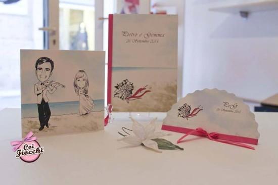 coordinato nozze personalizzato con le caricature degli sposi composto da partecipazione libretto messa e ventaglio con raso fucsia