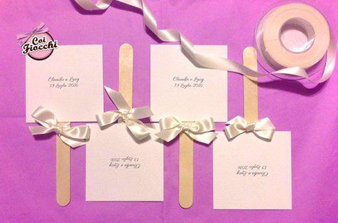 ventaglietti nozze per gli ospiti quadrati fatti in cartoncino e legno e impreziositi da un fiocco