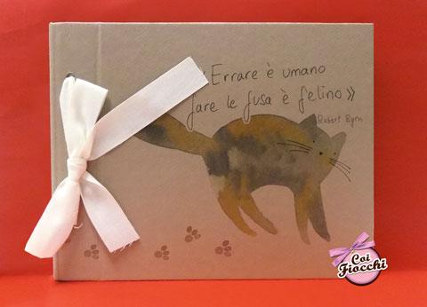 album-fotografico in carta kraft con fiocco bianco illustrato con gatto disegnato e citazione Errare è umano, fare le fusa è felino