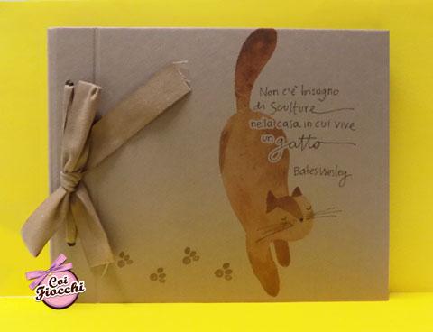 album-fotografico carta kraft con fiocco ecru illustrato con gatto rosso e citazione Non c'è bisogno di sculture nella casa in cui vive un gatto