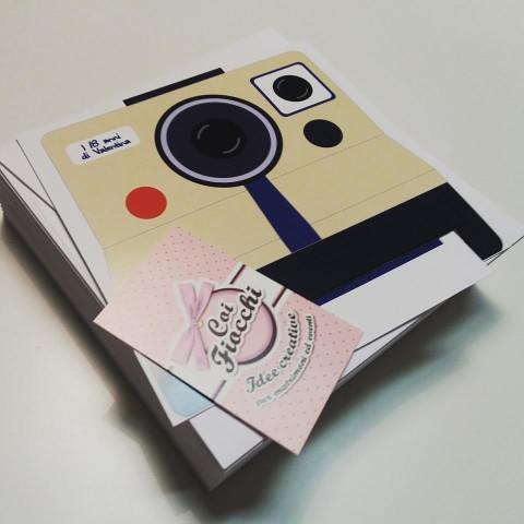 biglietto diciottesimo in formato polaroid da cui fuoriesce l'invito sotto forma di fotografia