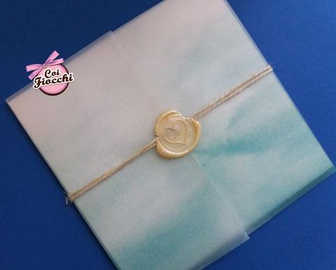 Partecipazione matrimonio a tema mare con onde su carta trasparente e ceralacca color oro