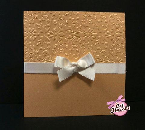 partecipzione di matrimonio elegante color oro con damasco a rilievo su carta perlata, chiuso da raso bianco
