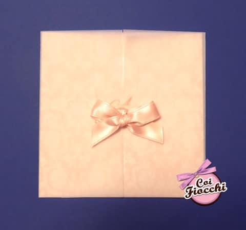 partecipazione color rosa pesca in carta perlata con decoro damascato e strado di carta semitrasparente e fiocco di raso