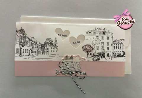 partecipazione di matrimonio a tema viaggio con sposini stilizzati in decappottabile e elegante landscape cittadino