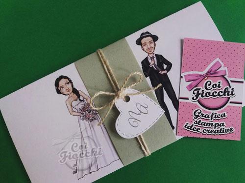 Partecipazione in stile shabby, con le iniziali inserite in un tag a forma di cuore e caricatura manga degli sposi.