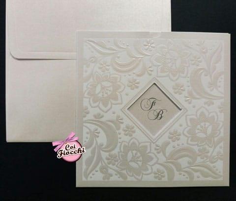 partecipazione-nozze-total-white con fiori in carta perlata e iniziali degli sposi che appaiono da un'apertura a rombo al centro dell'invito