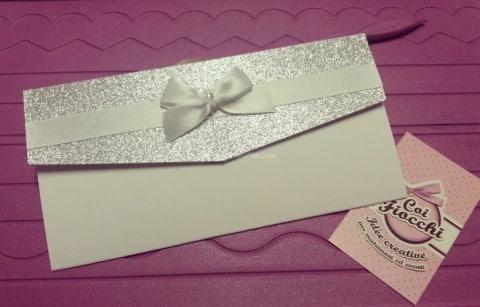 Partecipazione elegante total white a foglio unico con apertura glitterata e fiocco di raso bianco.