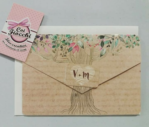 partecipazione albero della vita disegnato su texture legno e iniziali degli sposi scritte su un tag a forma di cuore