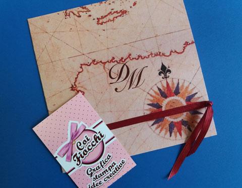 partecipazione di matrimonio a tema viaggio con iniziali degli sposi su mappa vintage e raso bordeaux