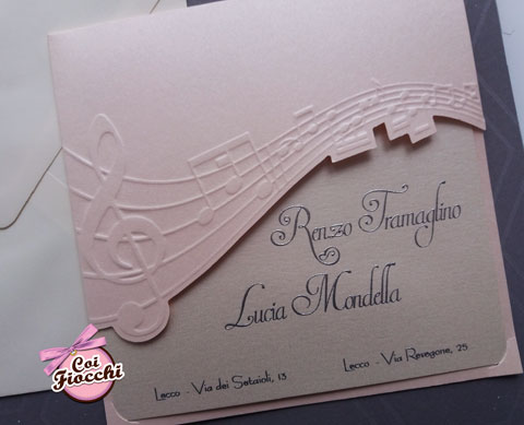 Partecipazione a tema musica con pentagramma fustellato sulla carta rosa antico e testo argentato a rilievo.