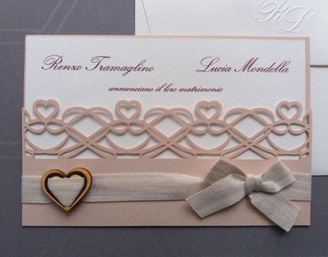 Partecipazione nozze rosa antico con ghirigori intagliati, fiocco e cuoricino applicato.
