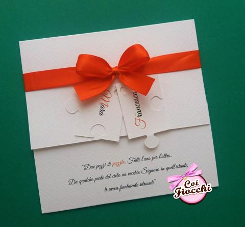 partecipazione nozze elegante con tessere di puzzle con i nomi degli sposi e fiocco